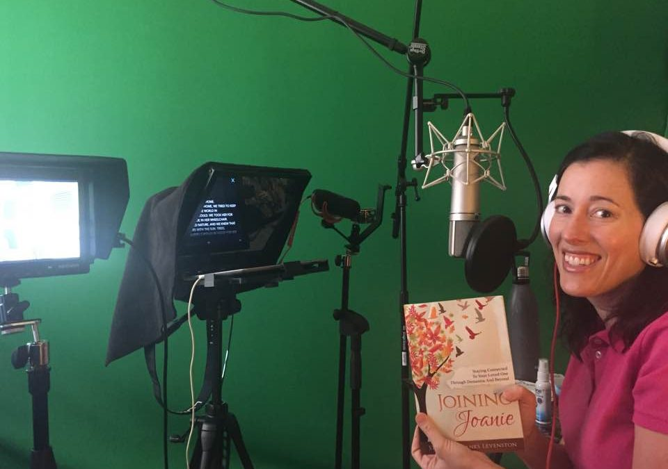 stephanie levenston in a recording studio holding her book joining joanie
